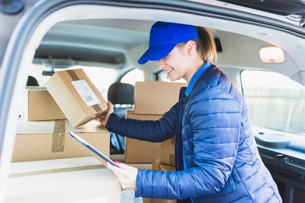 Dziewczyna z pastylką i pudełkami w samochodzie