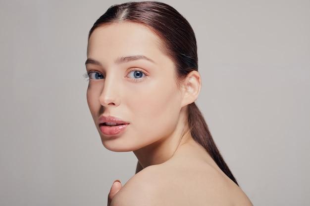 Dziewczyna z pełnymi ustami, ciemnymi włosami i promienną czystą delikatną skórą położyła dłoń na ramieniu, wyglądając prosto, siwo. podnosząca, zadbana kobieta. spa.