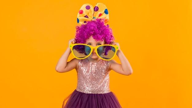 Dziewczyna z peruką klauna i dużymi okularami przeciwsłonecznymi