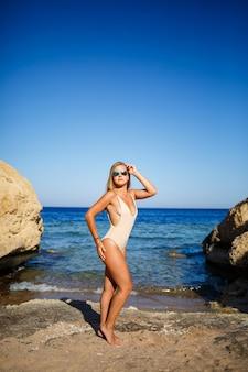Dziewczyna z piękną figurą w beżowym kostiumie kąpielowym w błękitnej wodzie morza czerwonego. stoi w jasnym słońcu