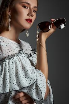 Dziewczyna z pięknymi kolczykami w uszach, portret piękna kobiety z biżuterią.