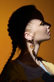 Dziewczyna z pięknymi kolczykami w uszach, portret uroda kobiety z biżuterią. idealnie gładka skóra