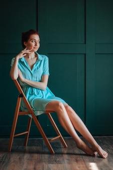 Dziewczyna z pięknymi nogami siedzi na krześle