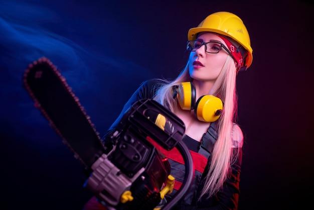 Dziewczyna z piłą łańcuchową w kombinezonie na czarnym tle w neonowym świetle