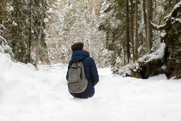 Dziewczyna z plecaka siedzi w ośnieżonym lesie iglastym.