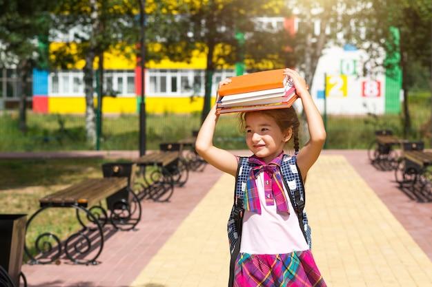 Dziewczyna z plecakiem i stosem książek na głowie w pobliżu szkoły. powrót do szkoły