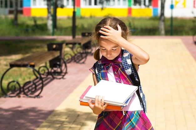 Dziewczyna z plecakiem i stosem książek w pobliżu szkoły. powrót do szkoły, dziecko jest zmęczone, ciężkie podręczniki. edukacja, klasy szkoły podstawowej, początek roku szkolnego, 1 września
