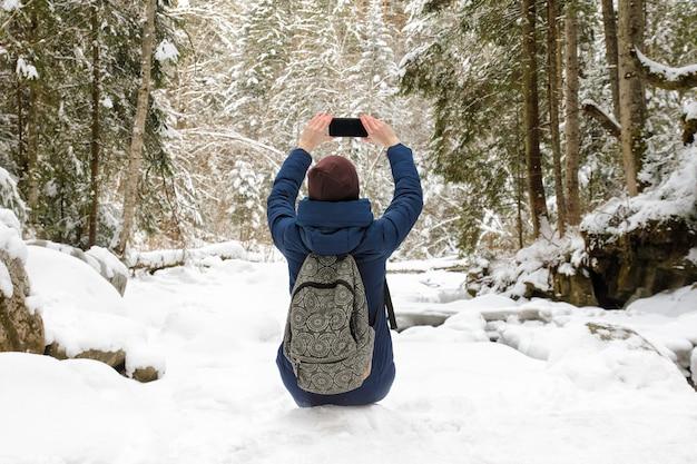 Dziewczyna z plecakiem siedzi w ośnieżonym lesie iglastym i robi zdjęcie na smartfonie.