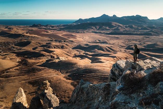 Dziewczyna z plecakiem stoi na skraju urwiska w górach z widokiem na dolinę o zachodzie słońca, widok od tyłu.