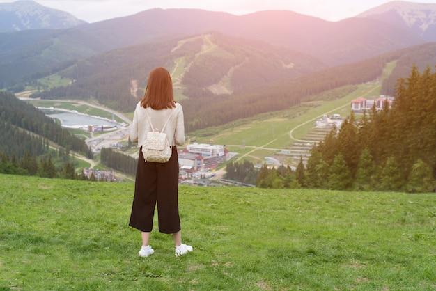 Dziewczyna z plecakiem stoi na wzgórzu i podziwia góry. miasto w oddali