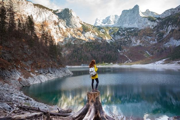 Dziewczyna z plecakiem stoi nad brzegiem górskiego jeziora