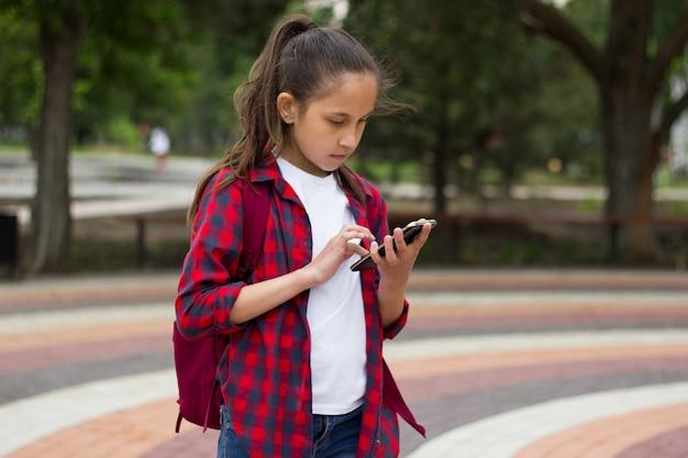 Dziewczyna z plecakiem w parku trzyma w dłoni telefon i używa go do komunikacji w komunikatorze