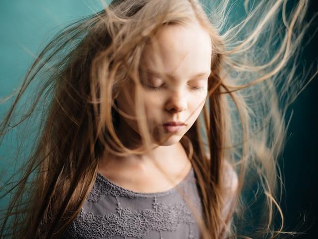 Dziewczyna z płynącymi włosami pozowanie zbliżenie zielone tło. zdjęcie wysokiej jakości