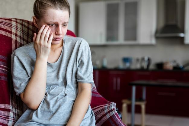Dziewczyna z podbitym okiem po walce z mężczyzną siedzi w domu na krześle i jest smutna, gdy dotyka rany. przemoc w rodzinie. agresja męża