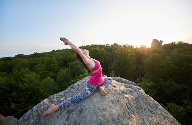 Dziewczyna z podniesionymi rękami robi rozciągające ćwiczenia jogi na szczycie ogromnej skały