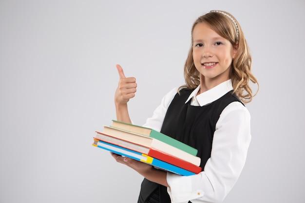 Dziewczyna z podręcznikami pokazuje znak klasy.