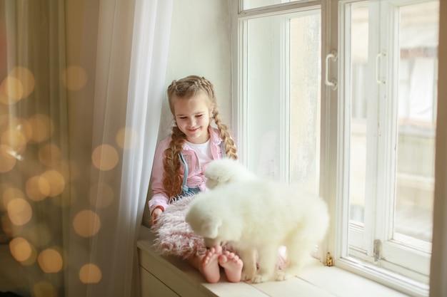 Dziewczyna z poduszką i białym szczeniakiem w ramionach.