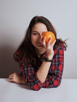 Dziewczyna z pomarańczowym uśmiecha się wygląda do aparatu, studyjny białe tło