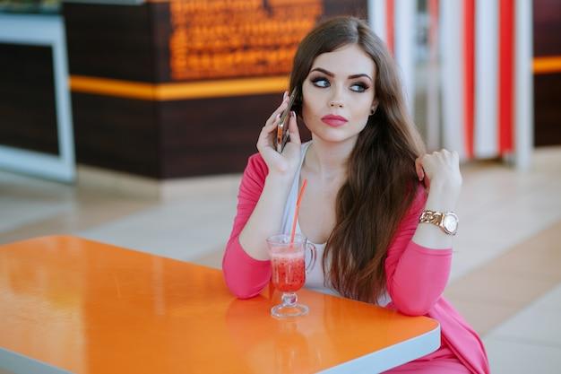 Dziewczyna z poważną twarzą rozmawia przez telefon siedzi w restauracji