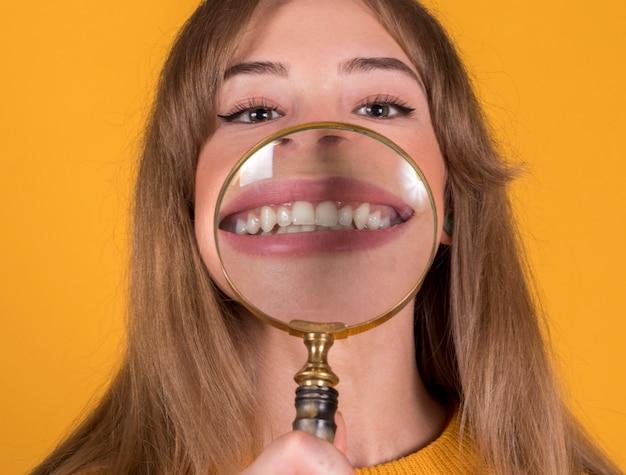 Dziewczyna z powiększać - szkło na żółtym tle
