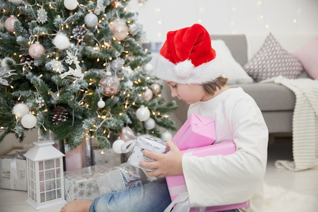 Dziewczyna z prezentami na choince w świątecznym salonie