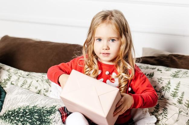 Dziewczyna z prezentem na kanapie. dziecko z prezentem świątecznym w domu. dziecko na boże narodzenie.
