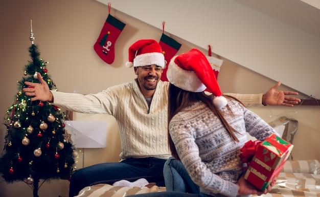 Dziewczyna z prezentem świątecznym za plecami, podczas gdy jej chłopak rozłożył ramiona w domu.