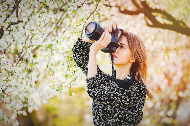 Dziewczyna z profesjonalnym aparatem fotograficznym, tworząc obrazy kwitnącego drzewa
