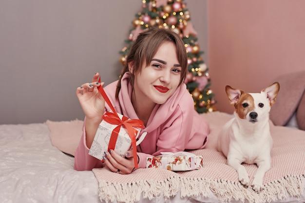 Dziewczyna z psem na bożenarodzeniowym tle. szablon kartki świąteczne. wesołych świąt i szczęśliwego nowego roku koncepcja.