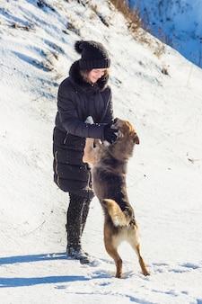 Dziewczyna z psem na spacerze w słoneczny zimowy dzień_