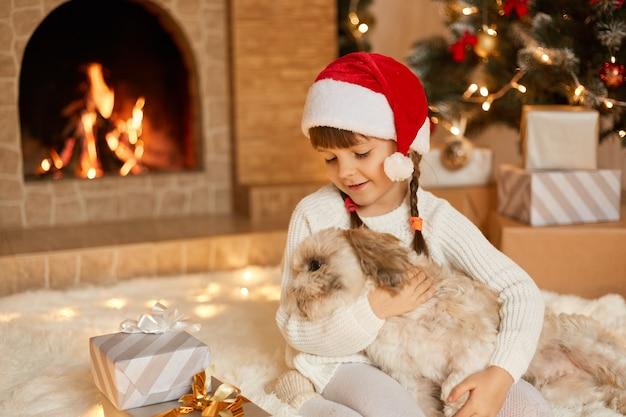 Dziewczyna z psem na sylwestra siedząc na podłodze kominku