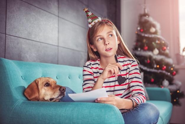 Dziewczyna z psem pisze liście życzeń na kanapie