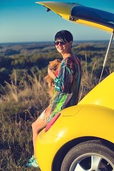 Dziewczyna z psem siedzi w bagażniku samochodu w polu o zachodzie słońca