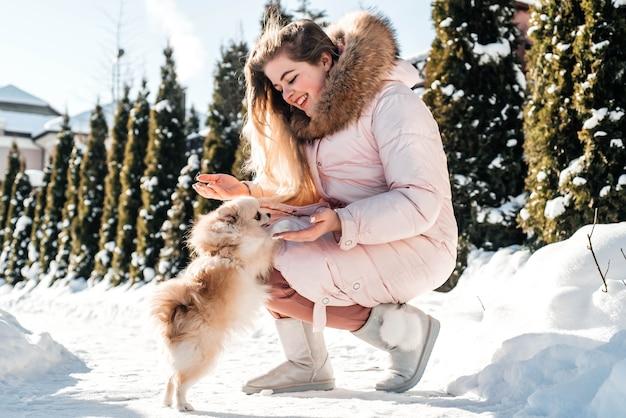 Dziewczyna z psem szpic szczeniak gra w zimie na świeżym powietrzu