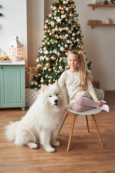 Dziewczyna z psem w pobliżu choinki na tle bożego narodzenia