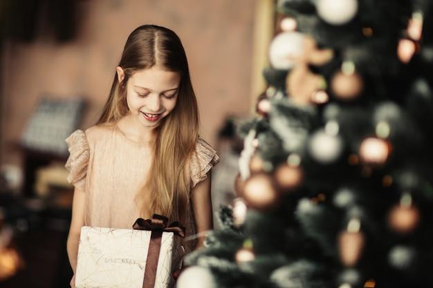 Dziewczyna z pudełkiem stojącym w pobliżu choinki.