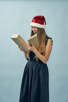Dziewczyna z pudełkiem w dłoniach i na sobie kapelusz świętego mikołaja