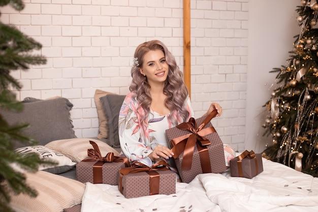 Dziewczyna z pudełkiem w domu w sypialni na boże narodzenie