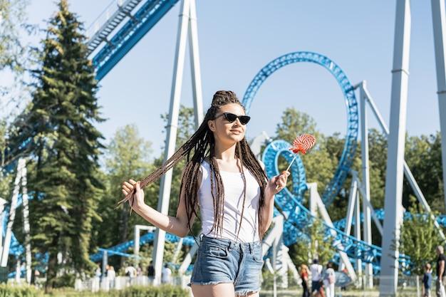 Dziewczyna z pudełkowatą warkocz fryzurą w parku rozrywki