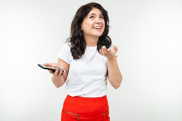 Dziewczyna z radością słucha muzyki przez głośniki swojego smartfona na tle białego studia z miejsca na kopię.