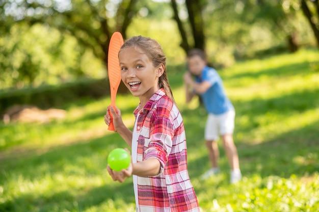 Dziewczyna z rakietą i piłką oraz chłopcy grający w tenisa