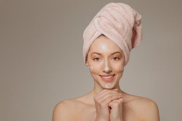 Dziewczyna z ręcznikiem na głowach uśmiecha się