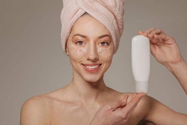Dziewczyna z ręcznikiem na głowie pokazuje śmietankę