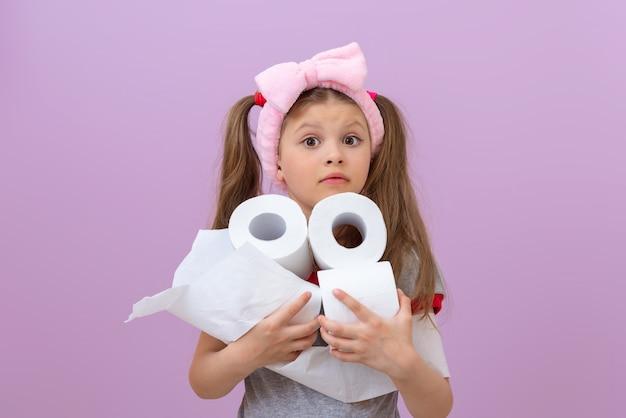 Dziewczyna z różową kokardką trzyma dużo papieru toaletowego.