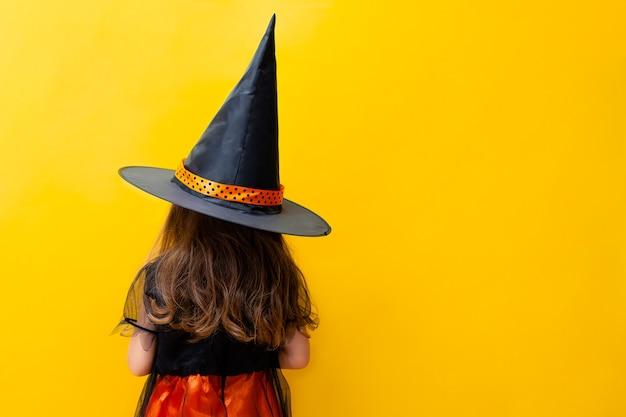 Dziewczyna z rozwianymi włosami w kostiumie wiedźmy stoi plecami
