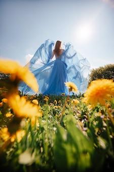 Dziewczyna z rudymi włosami w długiej niebieskiej sukience z dmuchawcem spaceruje latem po polu