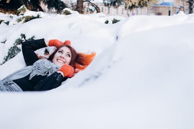 Dziewczyna z rudymi włosami w zaśnieżonym lesie zimowe wakacje nowy rok