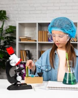 Dziewczyna z siatką na włosy robi eksperymenty naukowe z mikroskopem