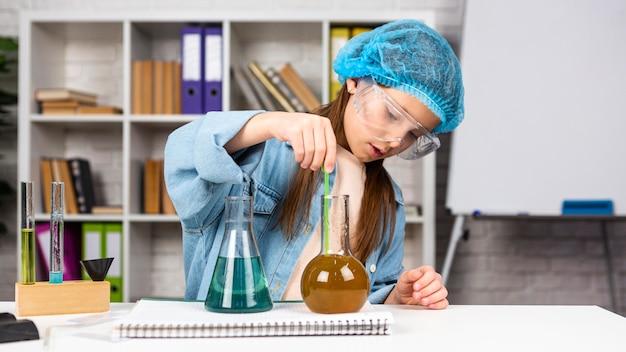 Dziewczyna z siatką na włosy robi eksperymenty naukowe z probówkami