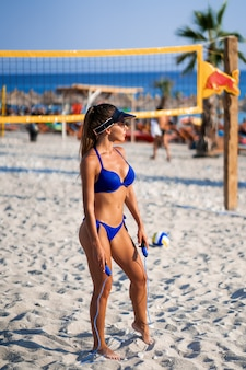 Dziewczyna z skakanka na plaży. sportowe szczęśliwa kobieta w modnym niebieskim seksownym stroju kąpielowym, ciesząc się słońcem ćwiczeń. zdrowy tryb życia. doskonałe kształty ciała fitness.